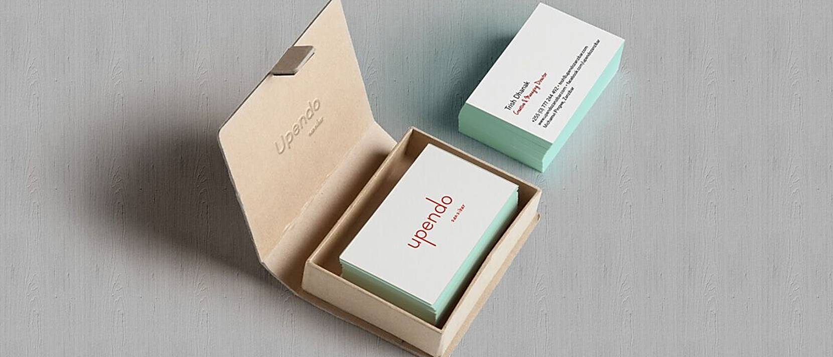 stack of cbusiness cards inside box with lid open and stack of business card on their own to the side