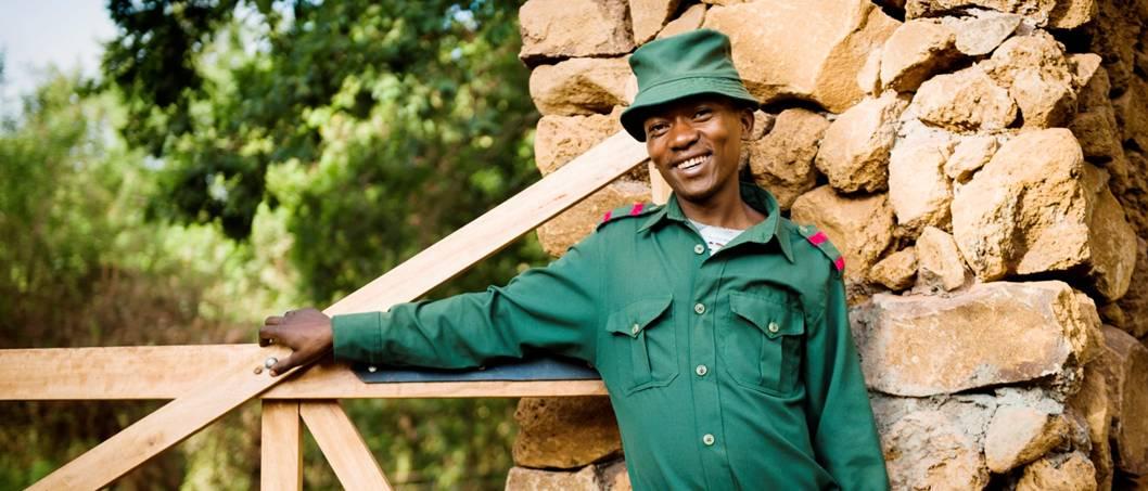 wooden gate, guard, bricks, stones, smiling man